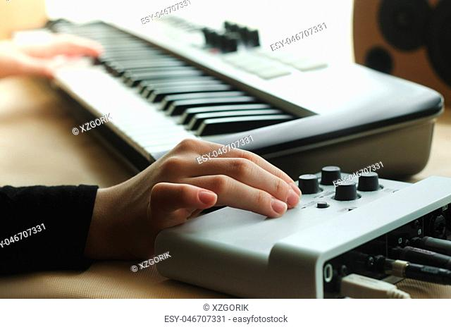 woman adjusts the synthesizer on the music console