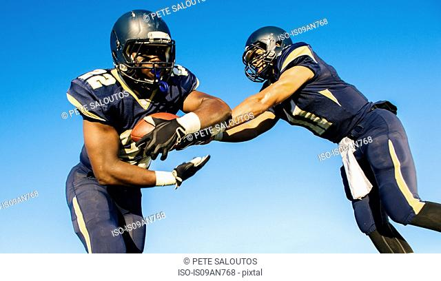 Two teenage american football players tackling ball