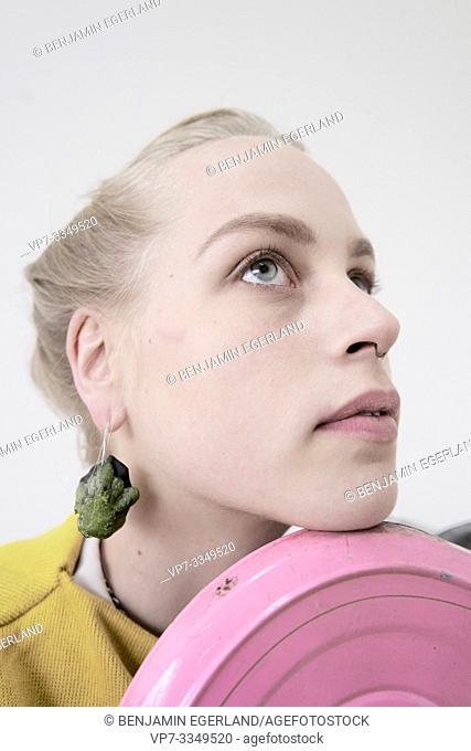 young woman wearing earrings made of raw zucchini