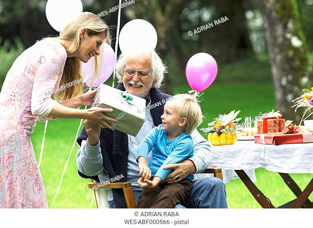 Grandfather receiving gifts on birthday party in garden