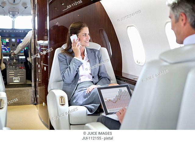 Businesswoman on phone and Businessman with digital tablet having meeting on private jet