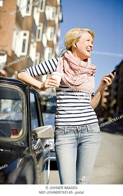 Woman using a mobile phone by a car, Sweden