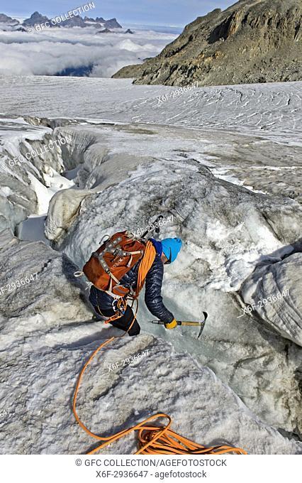 Alpinist examing a crevasse on the Plateau du Trient, Valais, Switzerland