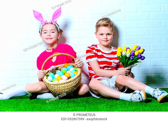 Cute happy children wearing bunny ears sits with Easter eggs and flowers on a green grass. Kid's fashion. Easter holidays