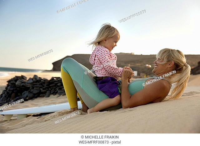 Spain, Fuerteventura, happy mother and daughter on the beach next to surfboard at sunset