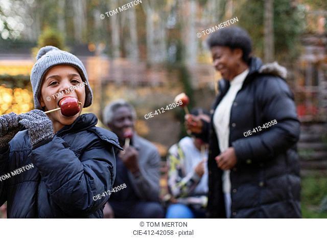 Portrait eager boy eating candy apple in backyard