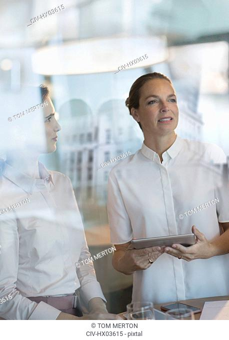 Businesswomen with digital tablet looking away in office