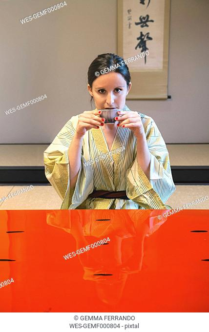 Portrait of woman wearing yukata drinking tea in a traditional Japanese room