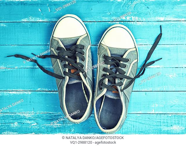 old worn textile sneakers with black laces on a blue wooden background, top view