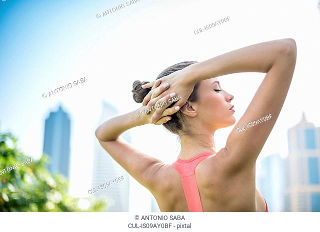 Woman training, eyes closed with hands behind head in park, Dubai, United Arab Emirates