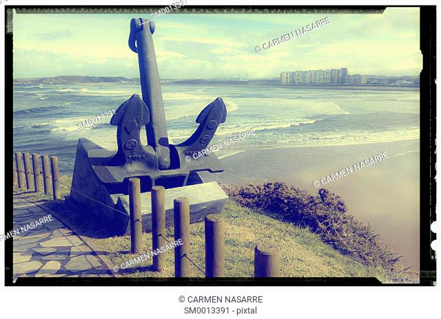 Salinas beach with an anchor in the foreground view from the Philippe Cousteau museum, Salinas, Asturias