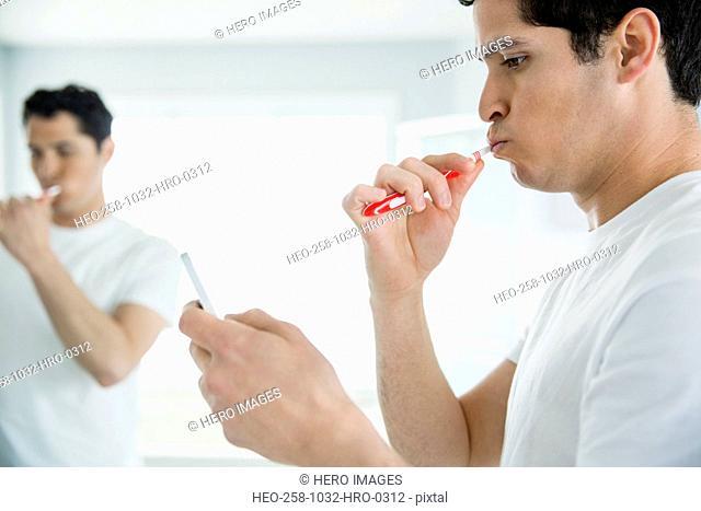 Man checking mobile phone while brushing teeth
