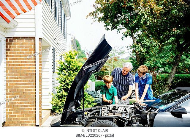 Caucasian grandfather and grandsons repairing car in driveway