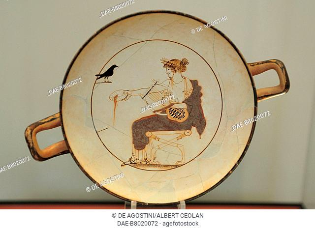Attic white-ground kylix depicting Apollo performing a libation and holding a lyre, ca 480 BC, clay, diameter 17,8 cm, discovered at Delphi, Greece