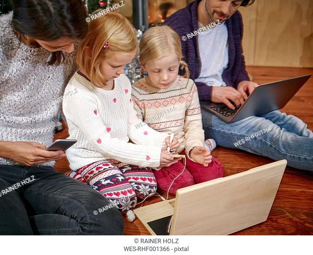 Father using laptop, mother playing with daughters on toy computer on Christmas Eve