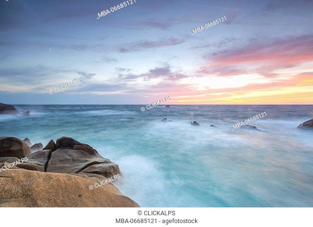 The fiery sky frames the waves crashing on rocks Capo Testa Santa Teresa di Gallura Province of Sassari Sardinia Italy Europe