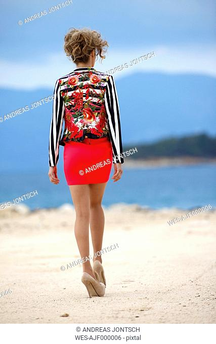 Greece, Young woman walking on sand at sea, close up