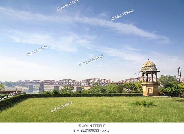 Green park and bridge under blue sky