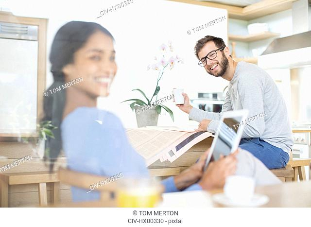 Couple relaxing with digital tablet, newspaper and coffee