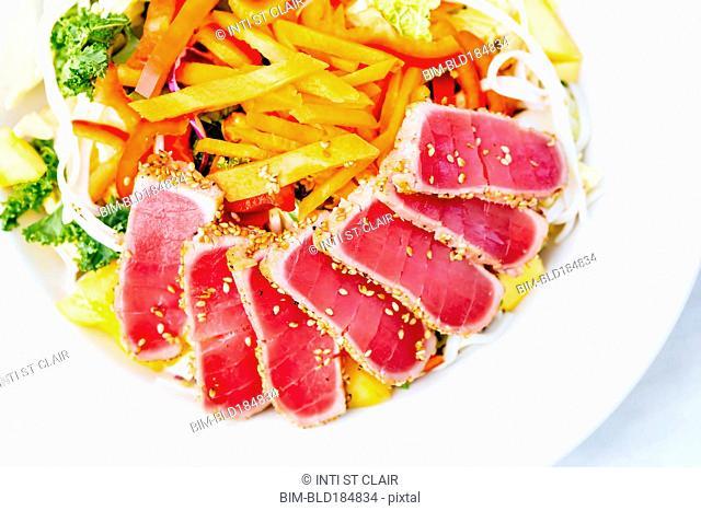High angle view of sliced tuna and salad