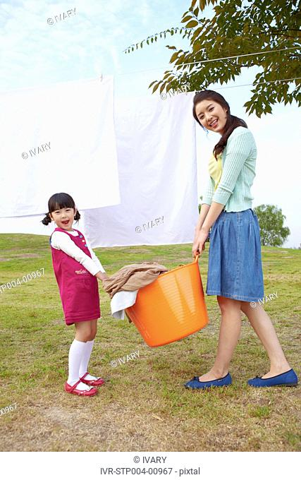 Mother And Daughter Carrying Laundry Basket