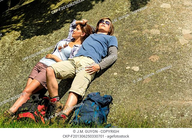 Resting Caucasian couple enjoying sunshine on rock backpack