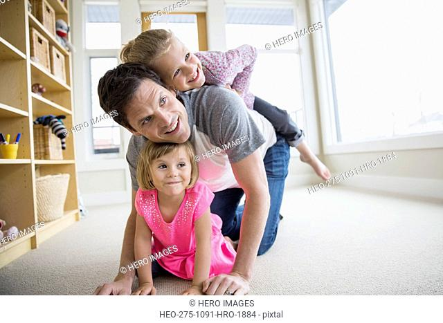 Father and daughters playing in living room