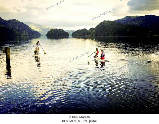 Girls paddle boarding on lake