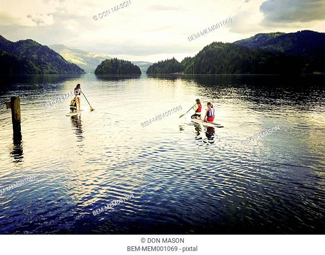 Girls paddle boarding on lake