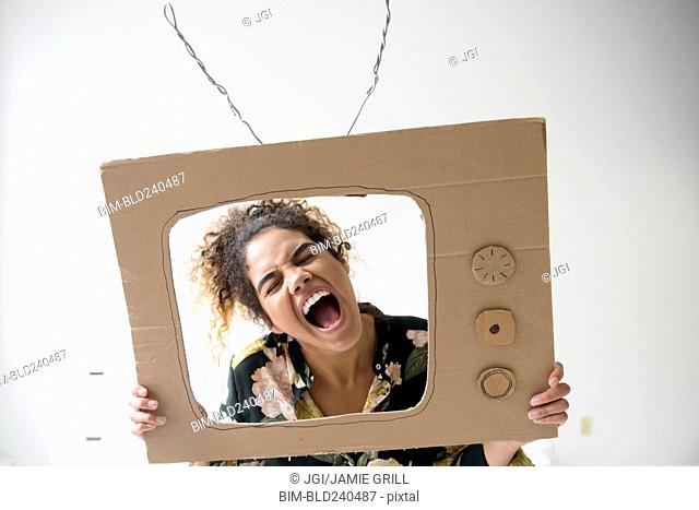 Mixed Race woman screaming in cardboard television
