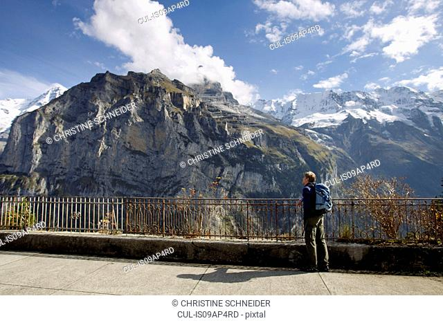 Male hiker gazing toward Nordwand of Mount Eiger, Murren, Grindelwald, Switzerland