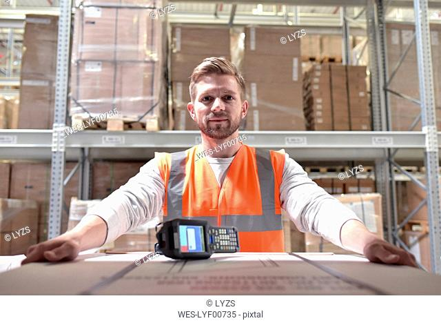 Portrait of confident man in factory hall with barcode scanner