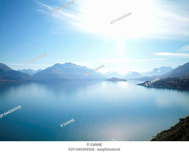 A still blue lake surrounded by mountains. Snow is on a few of them. There is a blue sky with white clouds, which is reflected in the lake