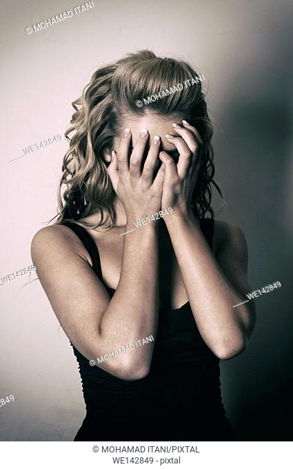 Young woman hiding face with hands