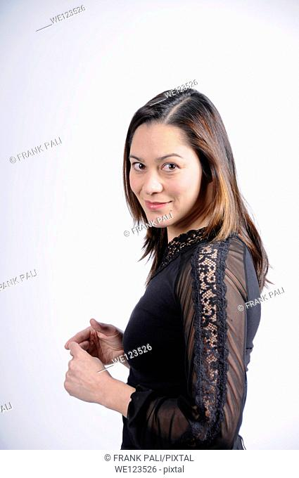 Young woman of filipino ethnicity is standing sideways and looking at camera