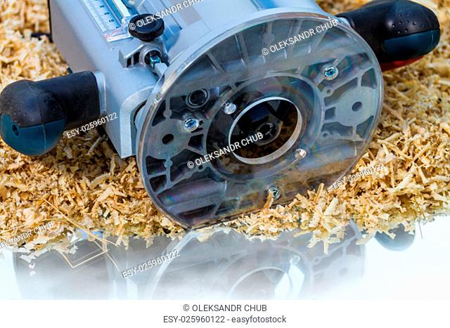 variable speed plunge router on sawdust background