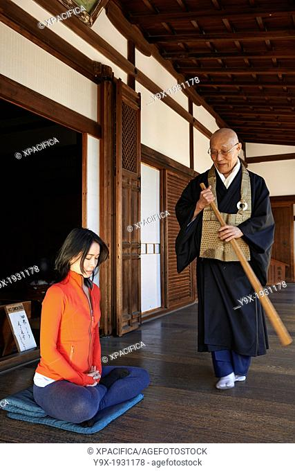 A priest blesses and meditates with an asian woman in the courtyard of the Garden of Solitary Sitting at the Zuiho-in, a sub-temple of the Daitokuji Monastery...