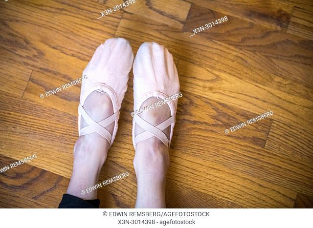 Girl points feet while wearing ballet slippers against wooden floor, Washington Grove, Maryland, USA