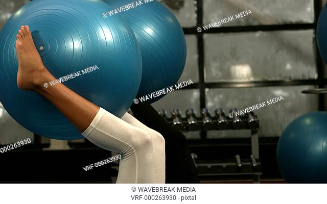 Women holding exercise balls up with their legs