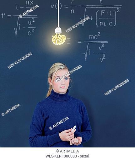 Schoolgirl in front of blackboard with formula