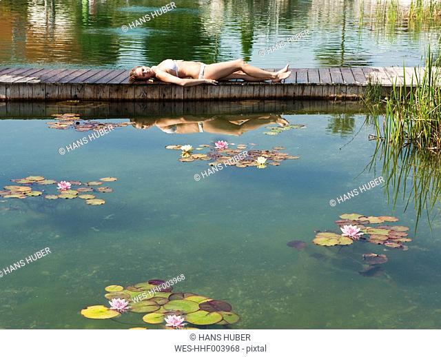 Austria, Salzburg County, Young woman lying on bridge near pool