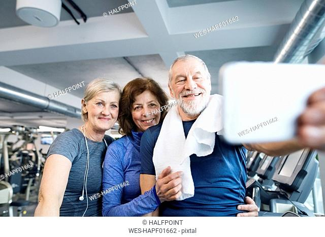 Group of fit seniors in gym taking a selfie with smartphone after working out