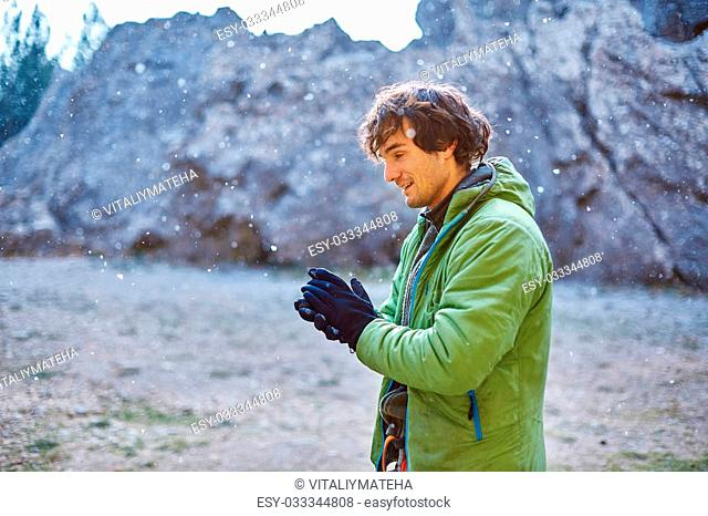 man rock climber preparing to climb under the cliff at winter