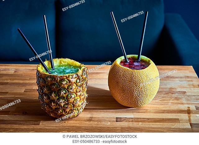 Coctail drinks with ice served in melon and pinapple on the wooden table in a pub. Copy space