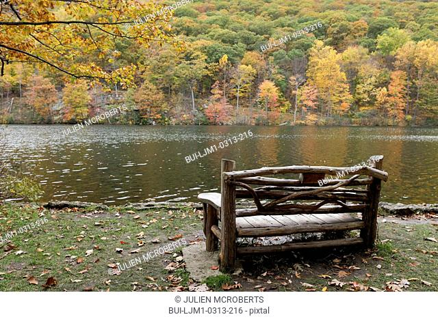 Empty bench facing lake at Bear Mountain park in the fall; New York; USA
