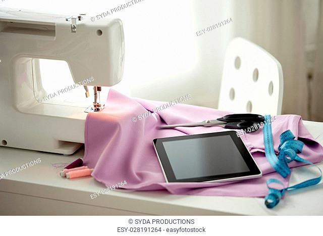 needlework, technology and tailoring concept - sewing machine with tablet pc computer, scissors, tape measure and fabric