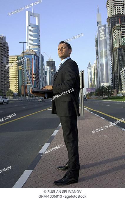 Businessman standing on Shaikh Zayed Road in Dubai and working on laptop
