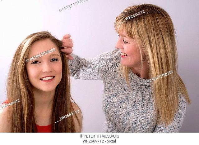 Teenage girl with her mother who is touching her hair