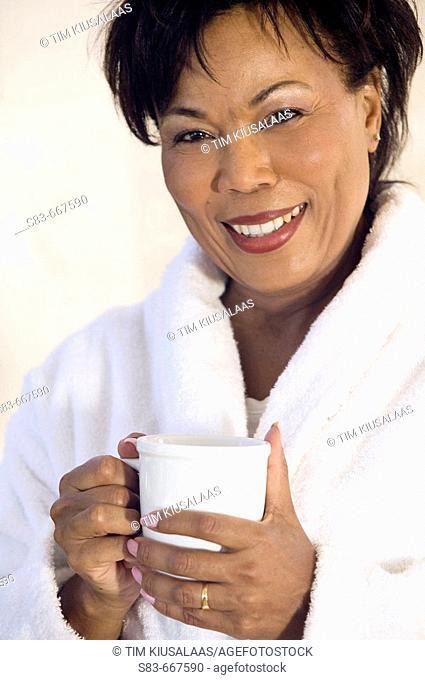 Senior woman in robe drinking coffee