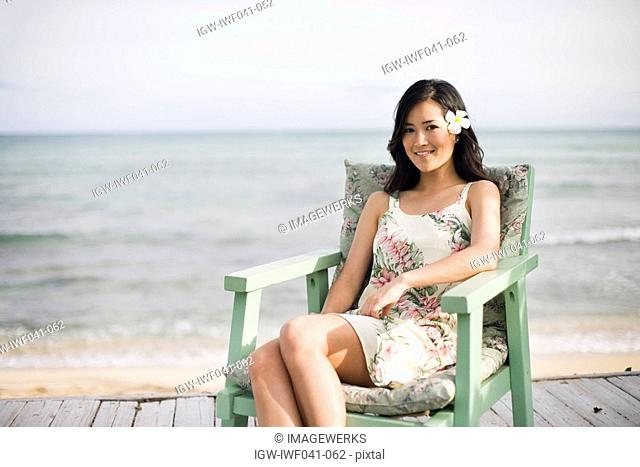 Portrait of a woman sitting on chair at beach